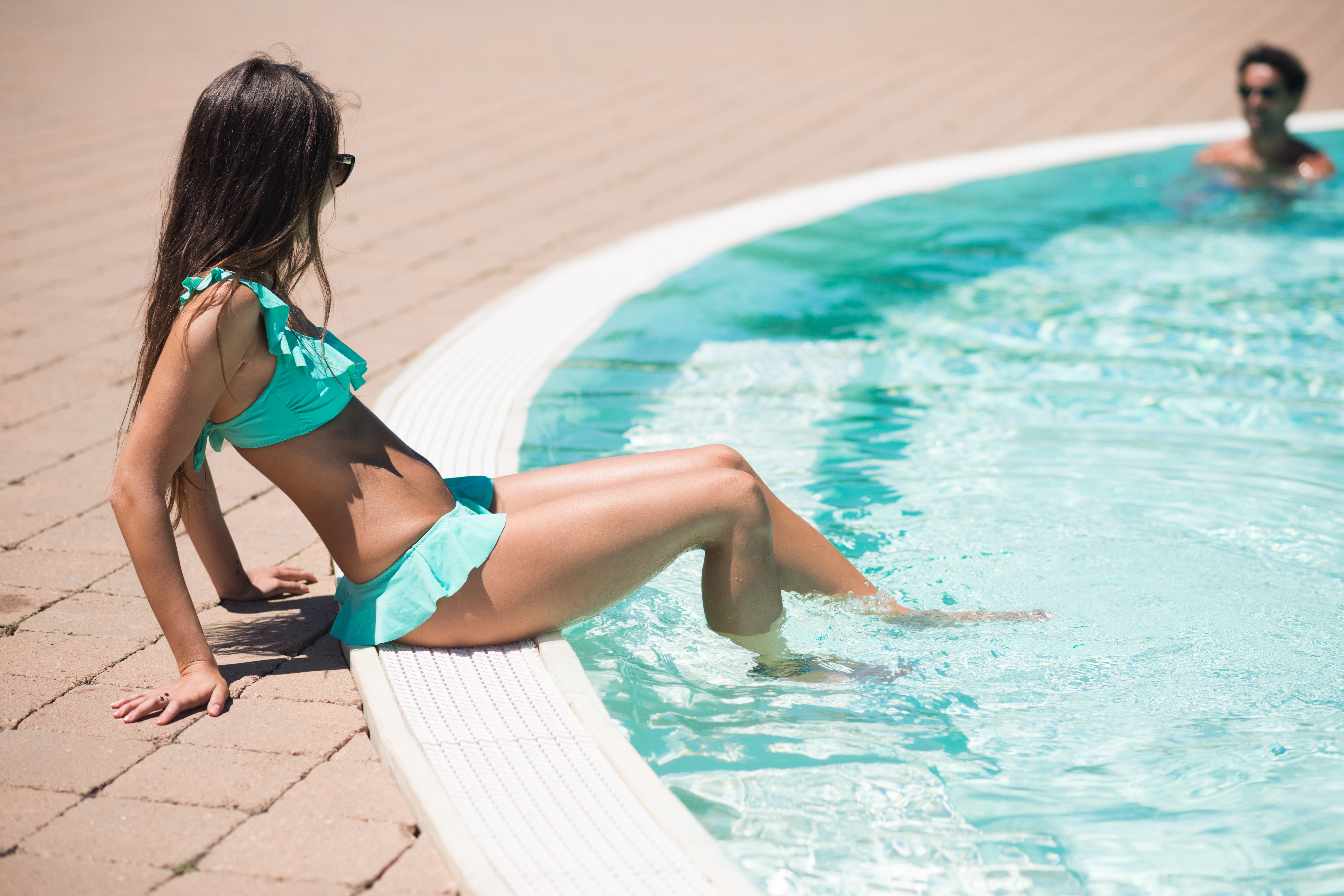 Woman refreshing her feet on the poolside