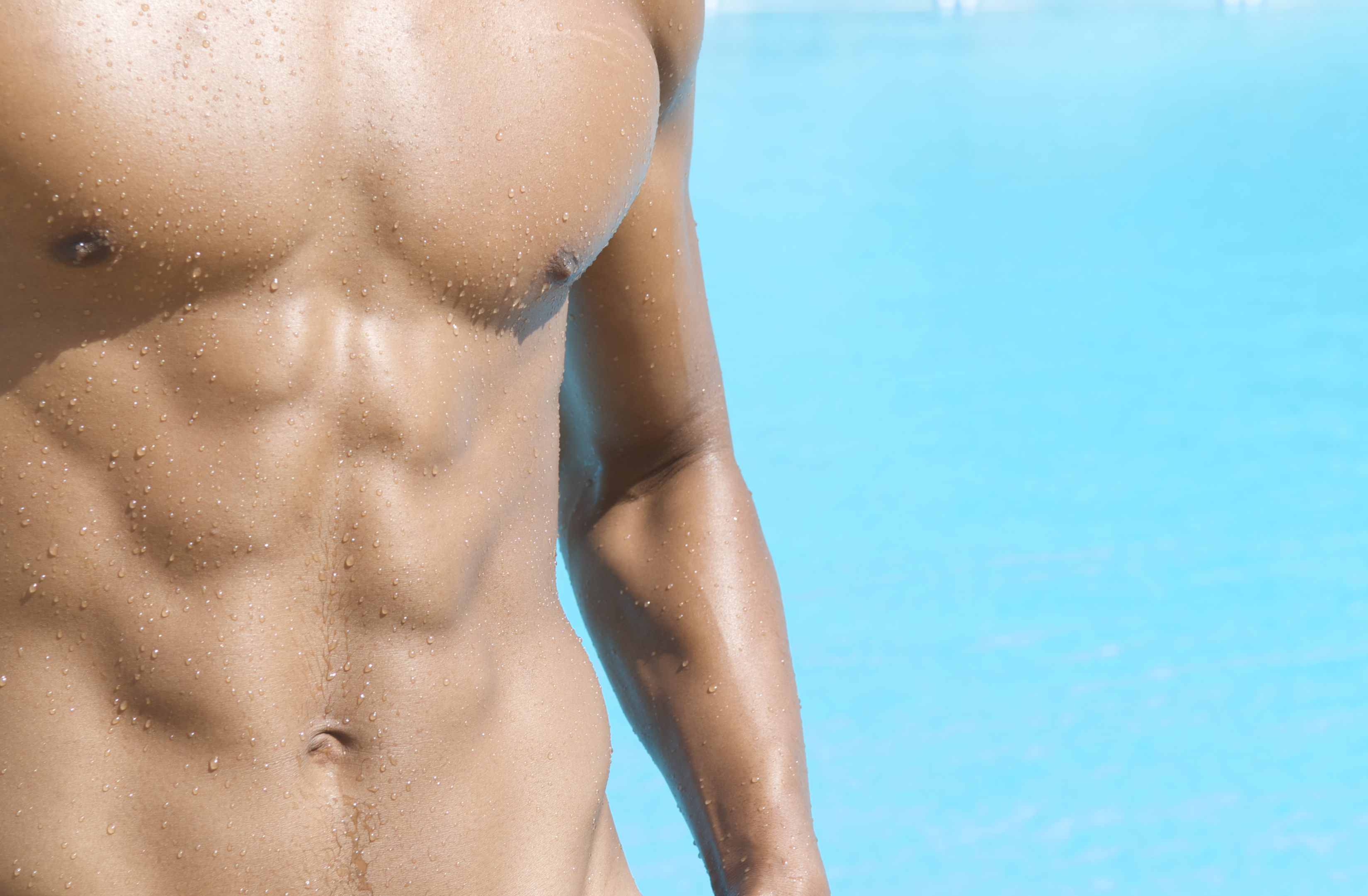 Muscular Athlete Stands in Sun at Swimming Pool
